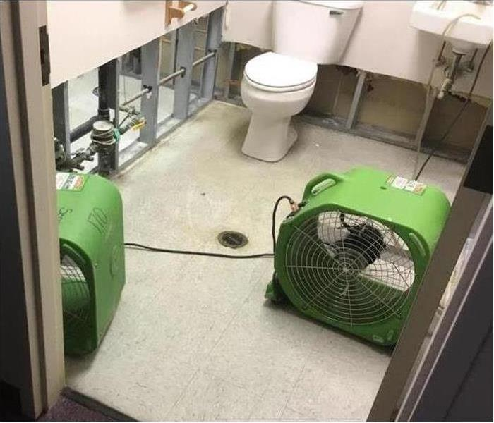 Fans set up in a bathroom because of an unchecked toilet